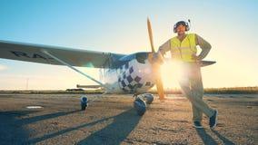 El aviador se levanta cerca de un aeroplano en un fondo del susnet, cierre almacen de video