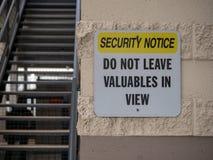 El aviso de la seguridad no deja los objetos de valor en placa de calle de la visión cerca de estacionamiento imagenes de archivo