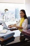 El ayudante de la mujer de negocios sonríe en la cámara que mecanografía en la PC Imagen de archivo