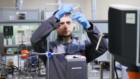 El ayudante de laboratorio en gafas mezcla el líquido en cubilete almacen de video