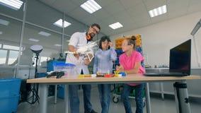 El ayudante de laboratorio está demostrando un quadcopter a los adolescentes almacen de metraje de vídeo