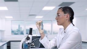 El ayudante de laboratorio femenino conduce pruebas de laboratorio de un líquido azul en un tubo de ensayo mientras que se sienta almacen de metraje de vídeo