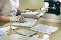 El ayudante de laboratorio registra los resultados de las pruebas en el registro, el microscopio y resultados de la prueba en la  imagen de archivo libre de regalías