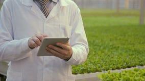 El ayudante de laboratorio se coloca con la tableta en manos en premisa del complejo agroindustrial almacen de video