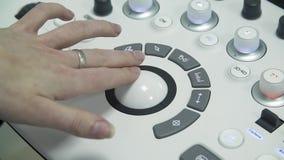 El ayudante de sanidad utiliza un escáner del ultrasonido El doctor tocó un regulador redondo Posesión del equipamiento médico almacen de metraje de vídeo