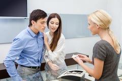 El ayudante de tienda ayuda a pares para elegir la joyería Imagen de archivo libre de regalías