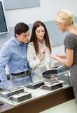 El ayudante de tienda ayuda a pares para seleccionar la joyería Fotos de archivo libres de regalías
