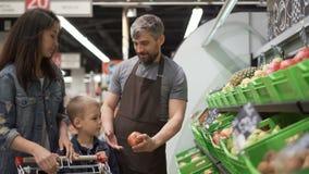 El ayudante de tienda experimentado está vendiendo la fruta a la mamá alegre y al niño jovenes de la familia, dándoles las peras, metrajes
