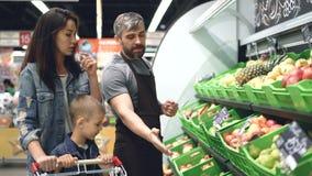 El ayudante de tienda hermoso sociable está vendiendo la fruta fresca a la mujer joven atractiva con el niño, hombre está señalan metrajes