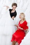 El ayudante de tienda ofrece otro vestido a la novia foto de archivo