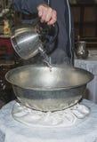 El ayudante del sacerdote llenó la fuente bautismal del bautizo de agua santa en la iglesia durante la ceremonia Imágenes de archivo libres de regalías