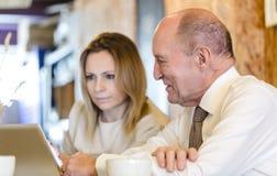 El ayudante personal adulto joven y el CEO mayor trabajan juntos Fotografía de archivo libre de regalías