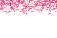 El azúcar asperja coloreado blanco y rosado en el fondo blanco Foto de archivo libre de regalías