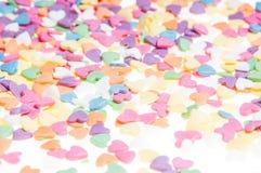 El azúcar asperja los corazones de los puntos, decoración para la torta y panadería, como fondo Fotografía de archivo