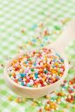 El azúcar colorido asperja en cuchara de madera imágenes de archivo libres de regalías