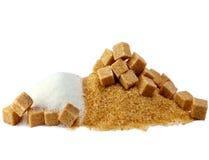 El azúcar granulado, azucara no refinado, caramelo de azúcar. Aún-vida en un fondo blanco Imagenes de archivo