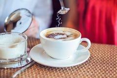 El azúcar vierte de la cuchara en el café, el hombre y la mujer sosteniendo las tazas, con los corazones en café Fotos de archivo