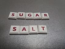 El azúcar y la sal de la palabra hechos de las tejas del crucigrama Foto de archivo