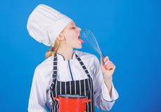 El azotar como favorable Muchacha en delantal que azota los huevos o la crema Comience lentamente a batir la crema que azota o de fotos de archivo