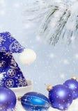 El azul adornado con el sombrero Santa Claus, la Navidad de los copos de nieve juega bolas azules y la rama nevada del pino Imagen de archivo libre de regalías