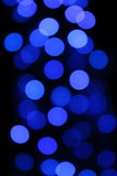 El azul azul de la guirnalda fuera de la iluminación oscura de la noche del bokeh del foco es círculos borrosos interesantes Foto de archivo
