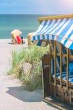 El azul bloqueado coloreado cubrió sillas en la playa arenosa en Travemunde, Alemania fotos de archivo libres de regalías