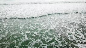 El azul de océano de la visión aérea y las ondas verdes se rompen en la playa blanca de la arena El mar agita en el abejón hermos almacen de metraje de vídeo
