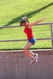 El azul de salto adolescente joven de la muchacha pone en cortocircuito la tapa roja Imagen de archivo