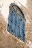 El azul descolorado anguloso shuttered la ventana con el sistema en una pared del yeso de la peladura - inclinación del tragaluz  fotografía de archivo
