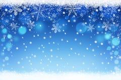 El azul hermoso empañó fondo del bokeh del cielo de la nieve de la Navidad y del invierno con los copos de nieve cristalinos