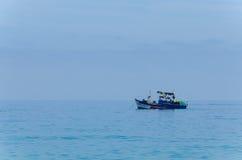 El azul pintó el pequeño barco de pesca delante de la costa angolana Fotografía de archivo libre de regalías