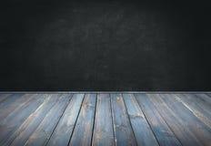 El azul pintó la tabla de madera con el fondo oscuro de la pared Imágenes de archivo libres de regalías