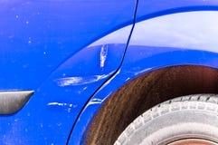 El azul rasguñó el coche con la pintura dañada en accidente del desplome en la calle o la colisión en estacionamiento en la ciuda fotografía de archivo libre de regalías