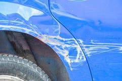 El azul rasguñó el coche con la pintura dañada en accidente del desplome en la calle o la colisión en estacionamiento en la ciuda foto de archivo