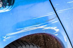 El azul rasguñó el coche con la pintura dañada en accidente del desplome en la calle o la colisión en estacionamiento en la ciuda imagen de archivo