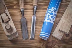 El azul rodó encima de los pernos prisioneros de madera de los cinceles de la alisadora del dibujo de construcción Fotografía de archivo