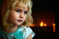 El azul rubio observó a la niña que se sentaba delante de una chimenea Imagen de archivo