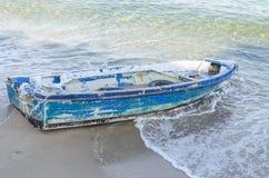 El azul viejo abandonó el barco de pesca en la playa de la arena Imágenes de archivo libres de regalías