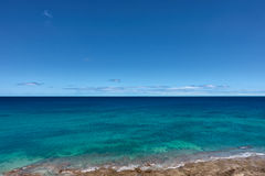 El azul y los turqois cristalinos riegan en la línea de la costa de Fuerteventura Imagenes de archivo