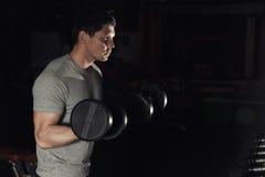 El bíceps de ejecución de In The Gym del atleta joven encrespa con pesas de gimnasia foto de archivo libre de regalías