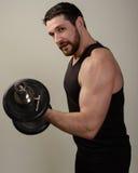 El bíceps de ejecución de In The Gym del atleta joven encrespa con pesas de gimnasia imágenes de archivo libres de regalías