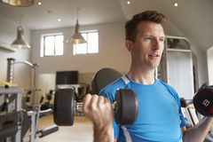 El bíceps practicante del hombre se encrespa con las pesas de gimnasia en un gimnasio, cierre para arriba fotos de archivo libres de regalías