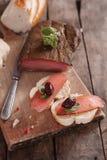 El búlgaro tradicional secó la carne adornada con pimienta y aceitunas rosadas Fotos de archivo libres de regalías