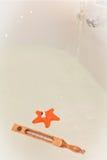 El baño blanco con un termómetro y el agua juegan Imagenes de archivo