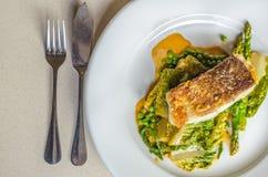 El bacalao asado a la parrilla con el espárrago y la ensalada se va en una placa blanca Imagen de archivo