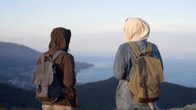 El backpacker acertado dos disfruta del paisaje hermoso en el pico de montaña metrajes