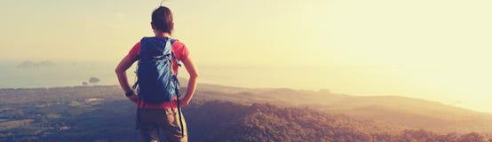El backpacker de la mujer disfruta de la opinión sobre pico de montaña imágenes de archivo libres de regalías