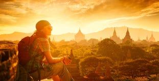 El backpacker de la mujer se sienta en puesta del sol y disfruta de la visión Foto de archivo