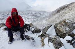 El Backpacker se vistió en capa roja y las gafas polarizantes que descansaban sobre su manera al campo bajo de Everest, Gorakshep Imágenes de archivo libres de regalías