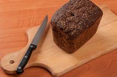 El baguette francés cortó en el tablero de pan de madera con el cuchillo Foto de archivo libre de regalías
